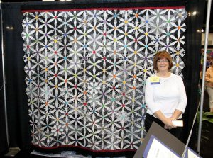 Kay standing with her quilt at Road to California